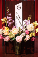 Hall of Fame sign on podium with flowers around base.
